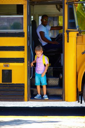 niños saliendo de la escuela: niño lindo está consiguiendo bajar del autobús, después de la escuela