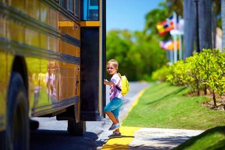 schattige jongen krijgt op de bus, klaar om naar school te gaan