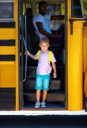 귀여운 아이가 방과 후 버스에서 내리고있다.