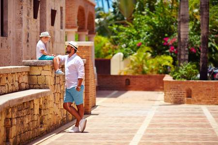summer wear: father and son having fun on cute tropical street
