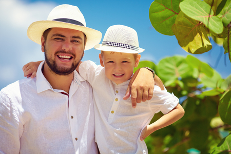 dominican republic: smiling father and son on summer vacation near the tropical seaside