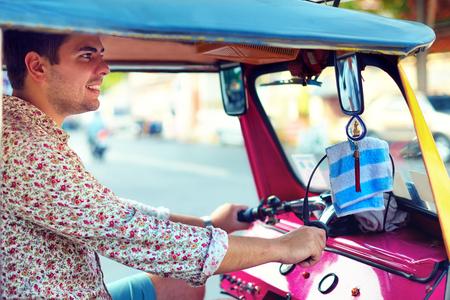 tuktuk: young adult man drives traditional asian transport tuk-tuk