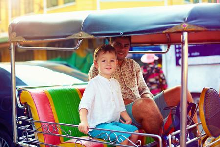 tuk tuk: happy tourist family travel through the asian city on tuk-tuk taxi Stock Photo