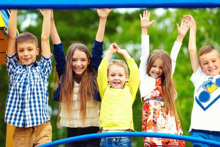 Enfants excités heureux de se amuser ensemble sur terrain de jeu Banque d'images - 56358271