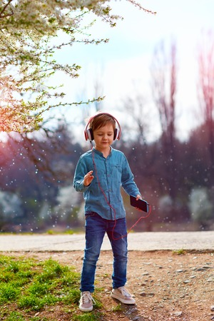 listens: cute kid boy with headphones listens to the music and dancing in blooming park