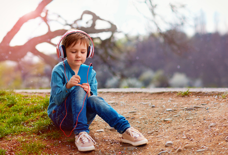 listens: cute kid boy with headphones listens to the music in  park