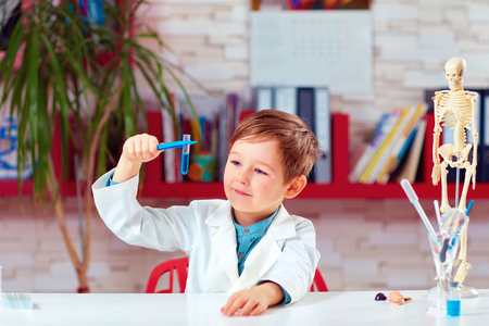 practical: little scientist making experiment on practical lesson in classroom
