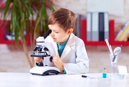 若い子供は学校の研究室で顕微鏡を用いた実験を行っています