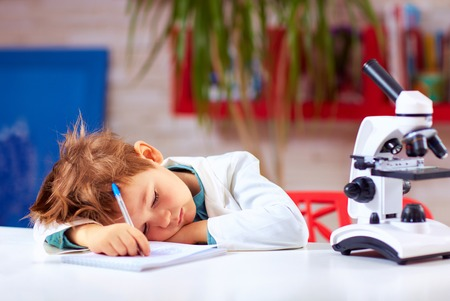 tired kid fell asleep after conducting experiment in school lab Stock Photo