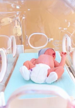 neonatal: newborn baby lying inside the infant incubator in hospital
