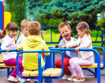 kids having fun: happy kids having fun on roundabout at playground