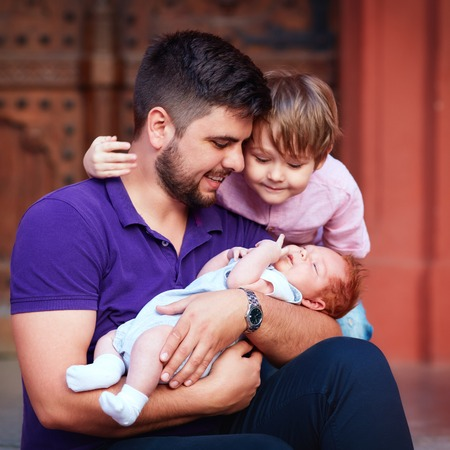 parentage: portrait of happy father with newborn baby and son