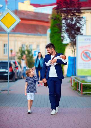 paternal: happy father, businessman walking with kids on city street