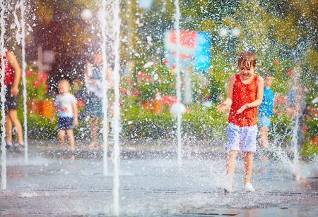 興奮した少年は、水滴、噴水の間楽しい時を過します。夏の市