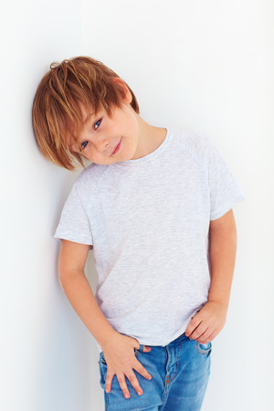 seven persons: handsome young boy, kid posing near the white wall