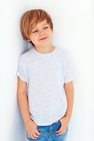6 7 year old: portrait of handsome young boy, kid posing near the white wall
