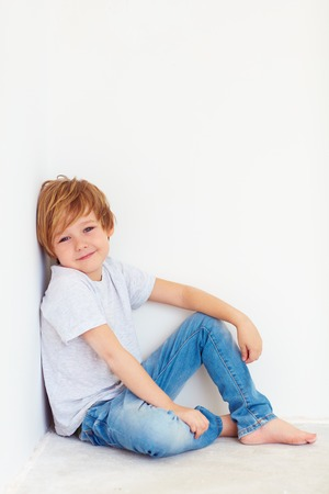 handsome young boy, kid posing near the white wall