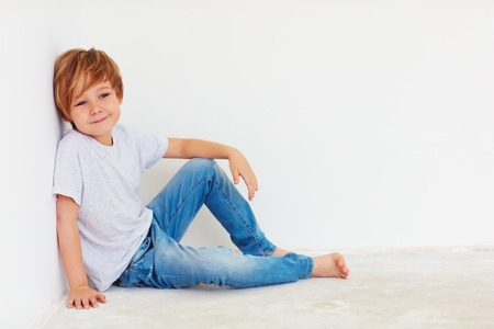 6 7 years: handsome young boy, kid sitting near the white wall Stock Photo