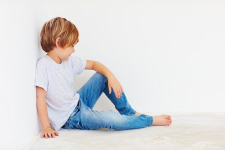 sitting on the ground: cute boy, kid sitting near the wall Stock Photo