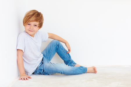 6 7 year old: handsome young boy, kid sitting near the white wall Stock Photo