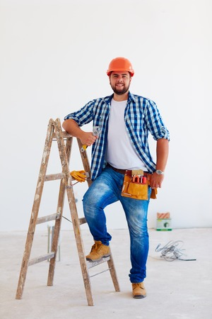 skilled labour: portrait of confident foreman, professional near ladder