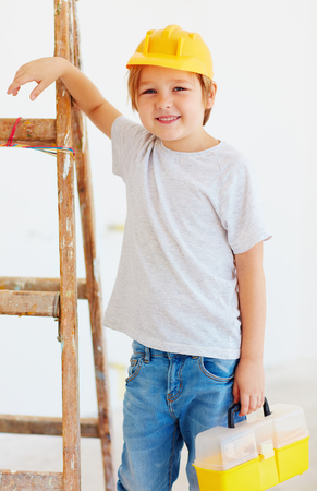 house robes: cute young boy, foreman standing near the ladder Stock Photo