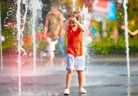 podekscytowany chłopiec zabawę pomiędzy strumieniami wody w fontannie. Lato w mieście
