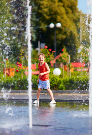 excited boy having fun between water jets, in fountain. Summer in the city Stock Photo