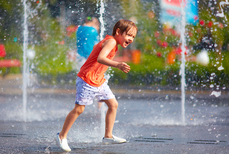 fountain: excited boy having fun between water jets, in fountain. Summer in the city Stock Photo