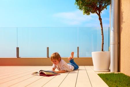 młody chłopiec, dziecko czytając książkę na tarasie na dachu, leżąc na patio Zdjęcie Seryjne