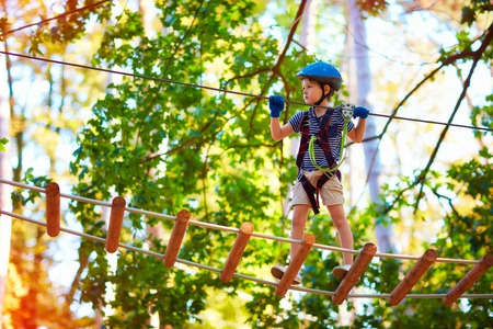 young boy passing the cable route high among trees, extreme sport in adventure park Foto de archivo