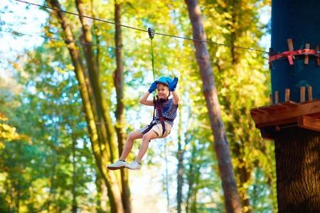 belay: young boy passing the cable route high among trees, extreme sport in adventure park Stock Photo