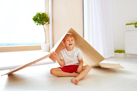 kidsroom: cute happy boy playing with cardboard box as with toy house Stock Photo