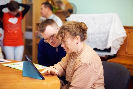 デジタル タブレットを見てリハビリテーション センターにおける障害者の 2 人の友人