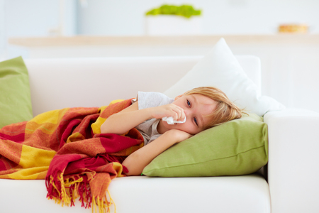 sick kid with runny nose and fever heat lying on couch at home Archivio Fotografico