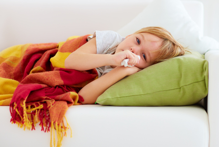 runny: sick kid with runny nose and fever heat lying on couch at home Stock Photo