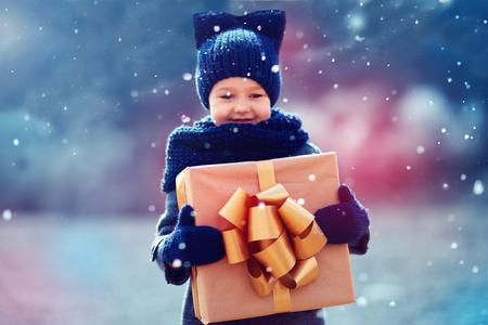 adorable Kind mit großen Geschenk-Box unter einem Schneefall. Konzentrieren Sie sich auf Geschenk-Box