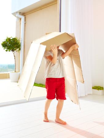 cajas de carton: cute happy boy playing with cardboard box at home