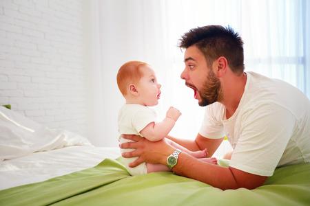 面白い父親と赤ちゃんは、驚きとお互いを見る