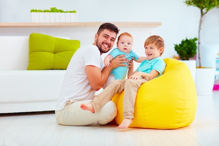paternity: happy father with six month and six years old sons, at home Stock Photo