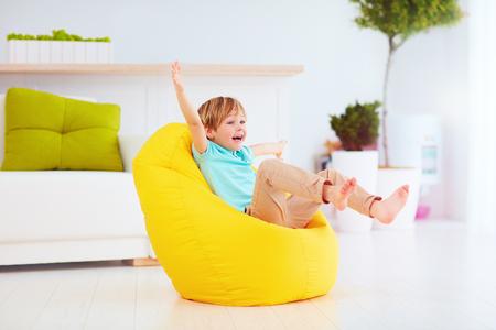 opgewonden jongen plezier, zittend op gele bean bag thuis Stockfoto