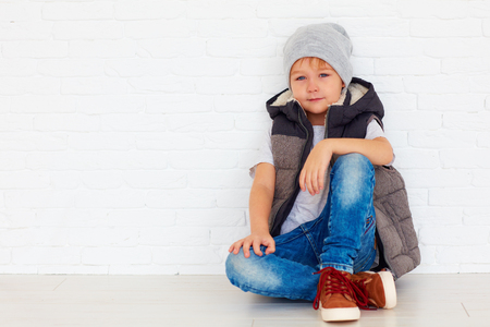portrait of fashionable kid near the wall Stock Photo