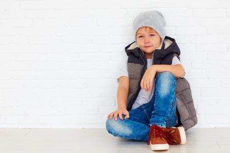 Portret van modieus kind dichtbij de muur