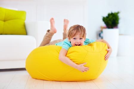 frijoles: cabrito feliz que se divierte en la bolsa de frijol amarillo en el hogar