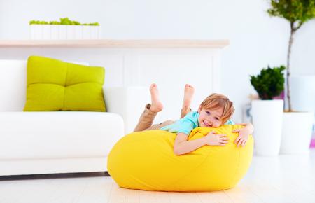 opgewonden kind plezier op gele bean bag thuis