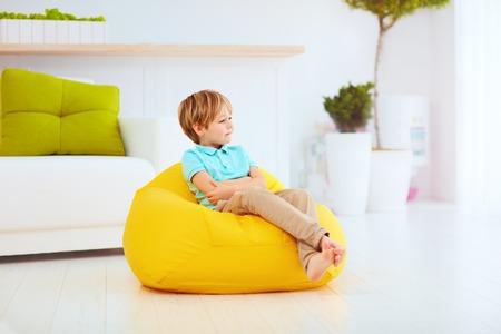 schattige jongen die zitten op gele bean bag thuis