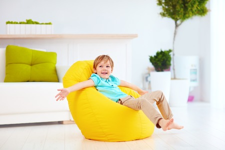 excited kid having fun, sitting on yellow bean bag at home Archivio Fotografico