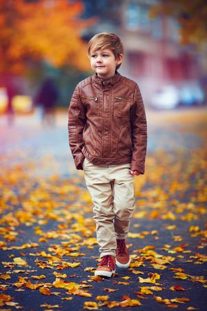 chaqueta: chico lindo caminar por la calle de la ciudad del otoño