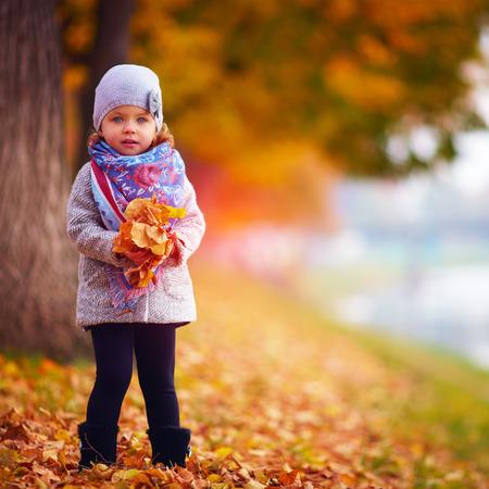 garments: adorable baby girl in autumn park