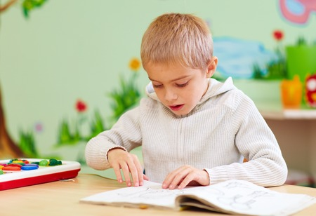 cute boy, kid with special needs looking at a book, in rehabilitation center Stock Photo